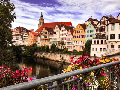 A view of Tubingen from the bridge over the river.  The timbered coloured houses line the river and the cathedral is behind in the background