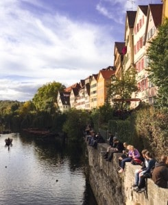 The river in Tubingen with people sitting on the wall beside it