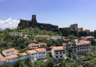 A view of Kruja with houses on the hill.  The fortress is on the top of the hill and the watchtower can be clearly seen.