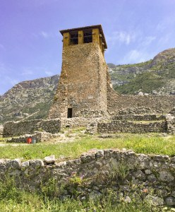 A view of the watchtower in the castle complex.  It sits on its own with grass at the bottom and hills/mountains in the background.  There are also parts of the old walls.