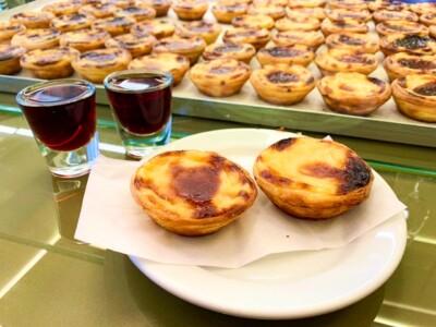 The wonderful pastel de nata that you must try on a Porto city break.  Two glasses of Portuguese liqueur sit alongside