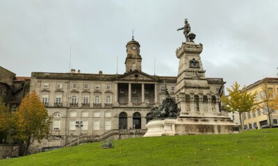 A view of the Praca Infant Dom Henrique.  This is a grassy area with a statue in the middle and a grand building in the background