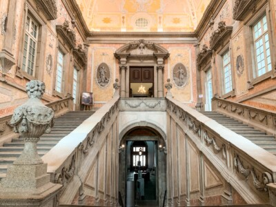 The ornate and decorated staircase in the Episcopal Palace.  The walls are pastel pink and the decorated ceiling is pastel pink and yellow.  There are stairs either side of a corridor and a bust at the bottom of the left hand staircase.