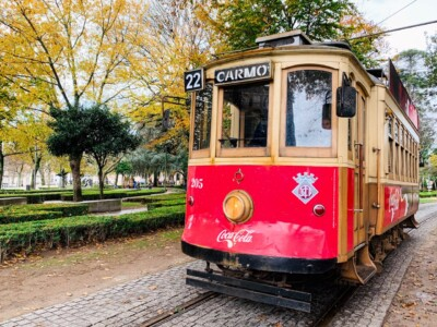 One of the old vintage trams that you can ride on a Porto city break.  It is red and sits to the side of a small park.