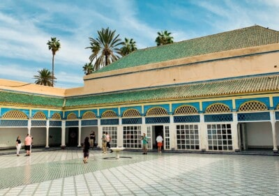 The large courtyard in the Bahia Palace, a top sight on short breaks to Marrakech.  The courtyard is wide with a surrounding blue and yellow pavilion with palm trees behind it