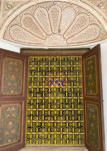 A door in the Bahia Palace.  The entrance is ornately decorated with wooden decorated door panels at the side.  Over the top of the door is a creamy geometric pattern