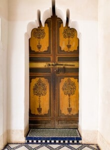 One of the doors in the Bahia Palace - a wooden door surrounded by white walls.  It has 4 pictures of trees on the door
