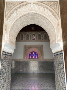 Looking into one of the rooms off the grand riad.  This has an archway - and this and floor and part of the wall in the room are adorned with tiny coloured mosaic tiles.  These is a small coloured stained glass window at the end