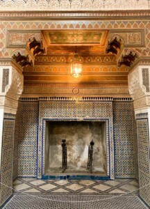 An ornate fireplace.  This is adorned with coloured mosaic tiles