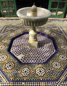 A small fountain in one of the outdoor areas.  On the floor are blue, yellow and green mosaic tiles in a circular pattern