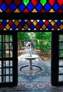 Looking out on the outside part of the large riad.  There is an open doorway with colourful stained glass above it and you can see the fountain on the pathway