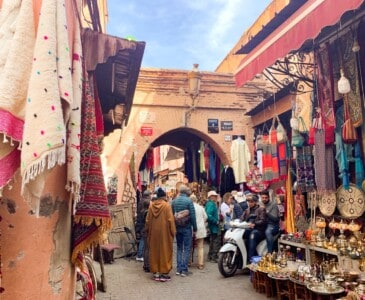 The souks in Marrakech that you will see on a short break to Marrakech.  This is a small street with stalls selling various wares that are hanging outside