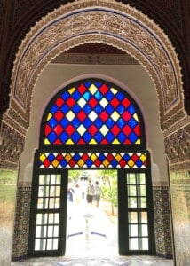Looking out on the outside part of the large riad.  There is an open doorway with colourful stained glass above it.