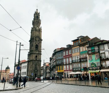The Torre dos Clérigos in Porto.  There are colourful buildings to side and tram lines in front