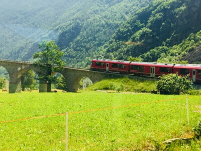 The Bernina Express red train going across a small viaduct in the countryside.  This trip is definitely one to put on your list of Europe trips 2021.