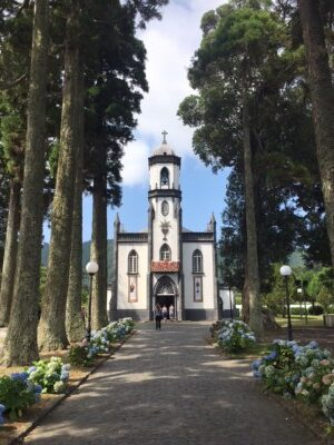 The small church in the town of Sete Cidades on Sao Miguel island in the Azores.  This is black and white and has a tree lined avenue leading up to it.