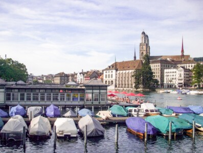 A view of the Frauenbad lido in Zurich.  Boats are moored besides it and you can see the Grossmunster church in the background