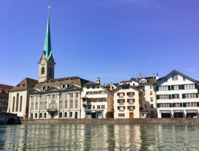 A view of the Fraumunster church in Zurich alongside the river.  You can see the tall, think, green spire