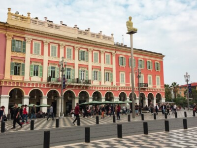 Part of Nice in France - you can see a smart orange coloured buildings with cafe bars outside.  The ground has black and white tiles