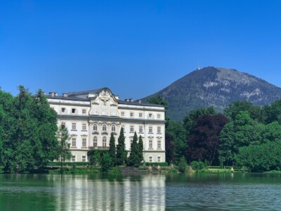 Schloss Leopoldskron which is just outside Salzburg city centre in Austria.  This is a large white villa that was used in the Sound of Music film and that sits on a lake.
