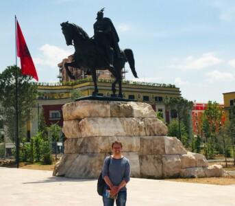 A picture of my partner in front of the Skanderbeg statue in Skanderbeg square in Tirana.