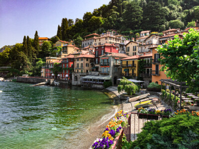 The bay in Varenna on Lake Como.  You can see the pretty colourful buildings with the trees behind.  A visit to Varenna is a must of you go to Lake Como one one of your Europe trips 2021