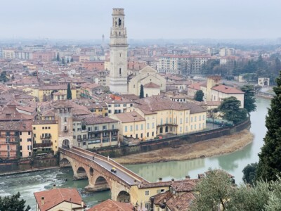 A view across Verona from high.  You can see the river with the bridge across it and the tower amongst the buildings.