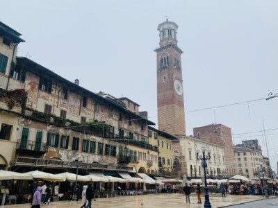 Here you can see the Torre dei Lamberti, a tall tower, that sits in the Piazza dell Erbe.  You can see bars and restaurants with outside seating.