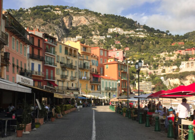 Part of the pretty town centre in Villefranche near Nice, France.  You can see cafe bars on either side of the road