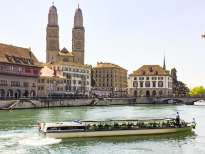 A boat going up the river Limmat in Zurich.  You can see the Grossmunster church in the background.  A boat trip os worth doing if you are in Zurich on one of your Europe trips 2021