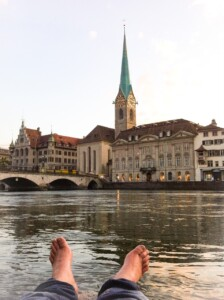 My partner's feet near the water in Zurich.  The Fraumunster church is in the background.  You can do this on one of your Europe trips 2021!