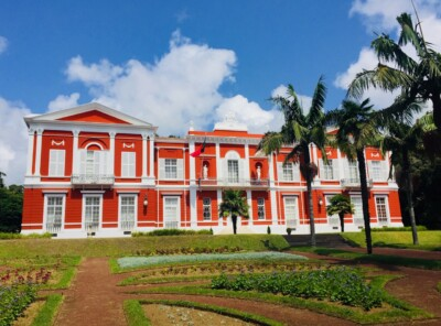 Here you can see a large villa in the gardens of Jardim do Palacio de Sant'Ana in Ponta Delgada in the Azores.  It is bright orange with white windows.  There are trees and manicured gardens in the foreground