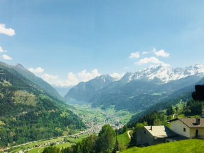 A view you can see on the Bernina Express train route.  You can see small houses on the hill in the foreground, then a valley with mountains in the background