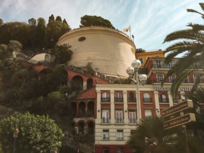 Part of Castle Hill in Nice France.  You can see buildings with the round viewpoint on the top.  There are lots of trees and bushes in the picture.