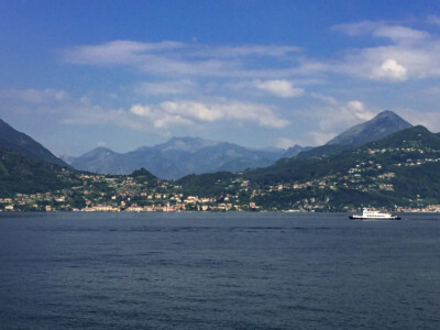 Lake Como with mountains in the background.  You can see a small ferry on the right.