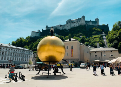 The Kapitelplatz square in Salzburg Austria with its large golden ball.  You can see the fortress high on the hill behind this.